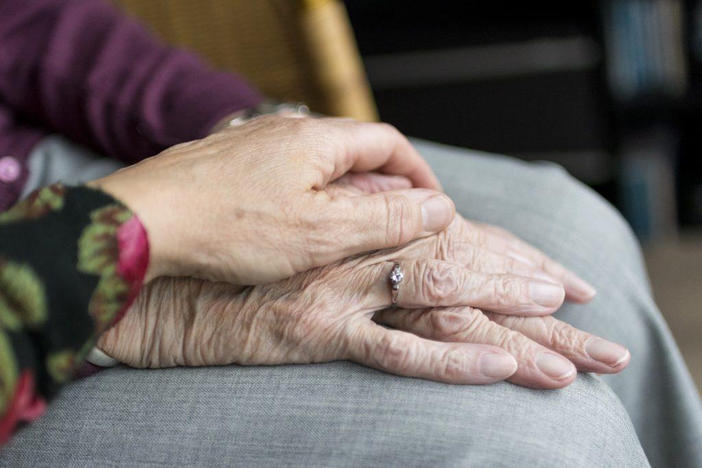 Handen van senioren op schoot.